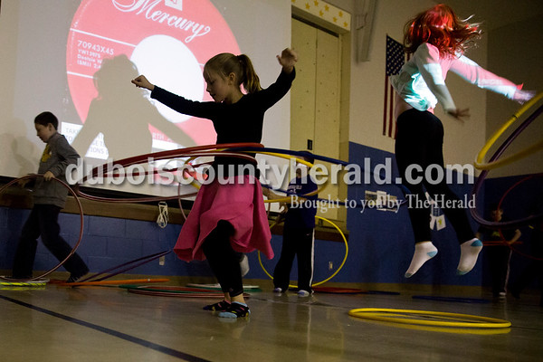 Sarah Ann Jump/The Herald David Turnham Educational Center fourth-grader Chloe Coleman, center, hula hooped as her classmate Ella Commens, right, jumped in the air during the annual PTO-sponsored sock hop at the school in Dale on Friday.