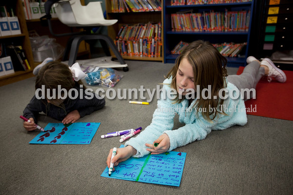 Alisha Jucevic/The Herald   Third-graders Haley Atkins, left, and Maggie Aull worked on cards to include with their car packages during class on Monday afternoon in Ireland.
