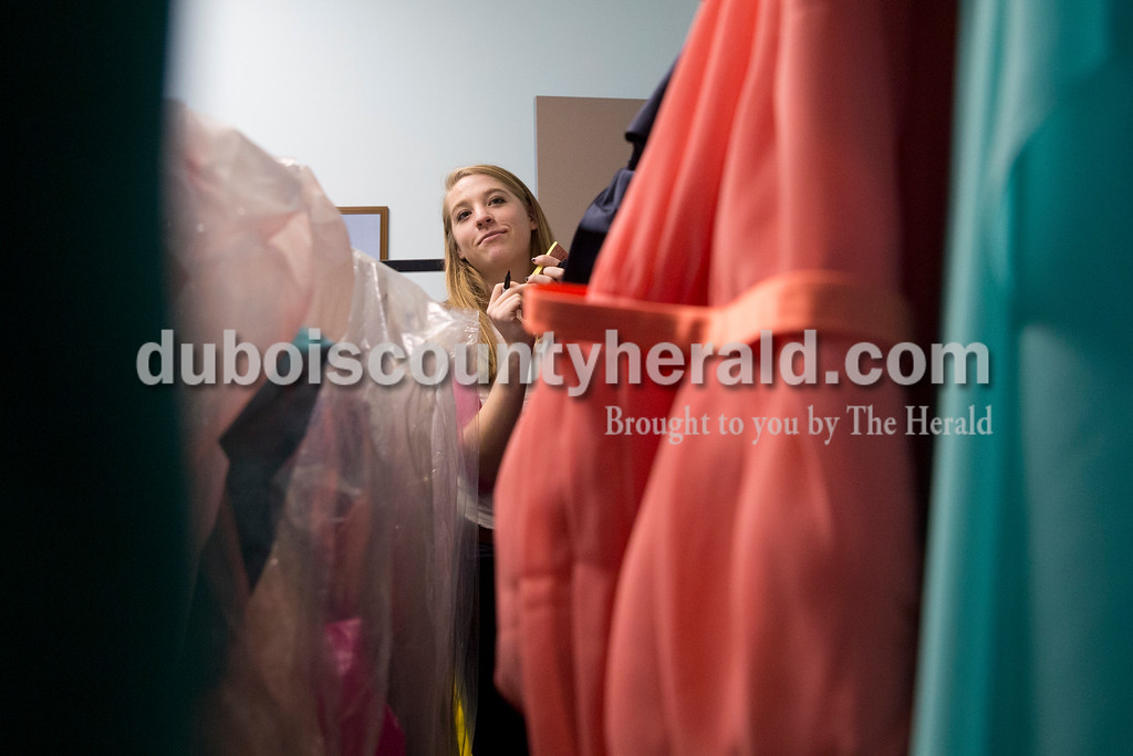 Sarah Ann Jump/The Herald<br /> Northeast Dubois High School junior Clare Mangin sorted prom dresses donated by school staff at the school on Monday. On Saturday, Mangin will host a dress drive from 11am to 3pm in the school's multi-purpose room.