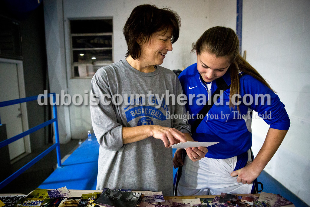 Former player and coach Beth Neukam showed photographs to her daughter Taylor Neukam, a freshman on the basketball team, after Monday's girls basketball game at Dubois Middle School. Beth coached the Jeeps girls basketball team from 1997 to 2001. Sarah Ann Jump/The Herald
