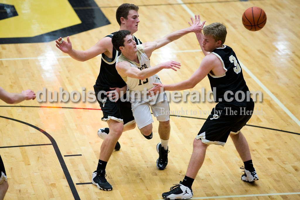 Jasper's Tyler Nottingham passed the ball to a teammate as Boonville's Nick Smith, left, and Ben Meier defended during Tuesday's basketball game in Jasper. Jasper defeated Boonville 69-59. Sarah Ann Jump/The Herald