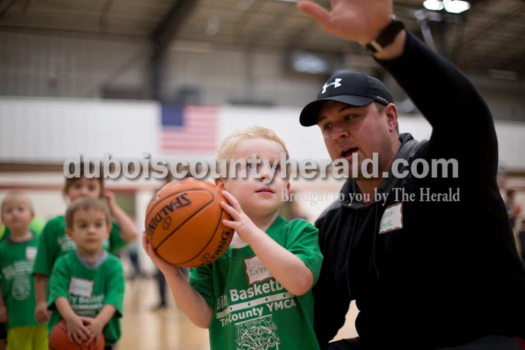 "Sarah Ann Jump/The Herald<br /> Everett Craig of Huntingburg, 3, listened to coach Derek Bolling of Huntingburg explain how tot shoot a basket during Bitty Basketball at the Tri-County YMCA in Ferdinand on Tuesday evening. The program teaches children ages 3 through kindergarten the basketball basics of shooting, passing, dribbling and defending, as well teamwork, sharing, listening and following directions. There are 147 players on 24 teams this year. ""You can see the improvement throughout the five-week program plus you can watch the friendships form,"" said program director Christine Kleaving."