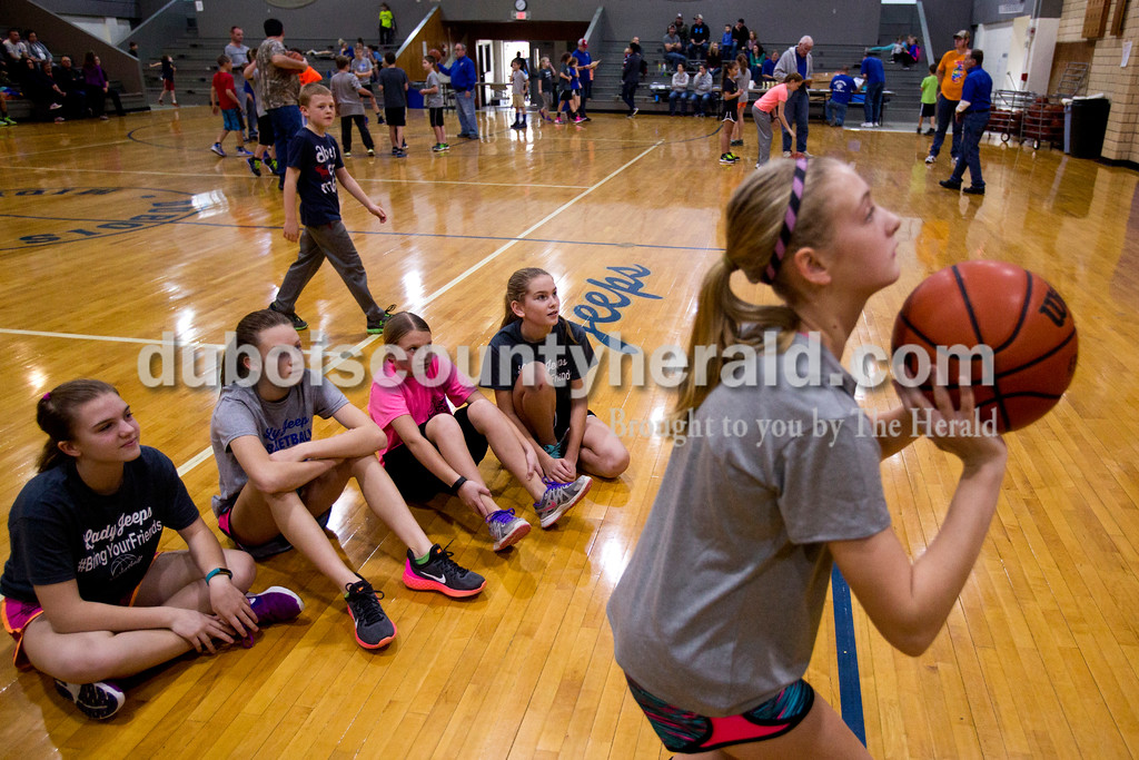 Tegan Johnston/The Herald<br /> From left, 11-year-old girls Emma Betz, Paige Wildman, Shayla Sander and Kelli Merkel, all of Celestine, watched as Sara Livingston of Haysville took her free throw shots during Sunday afternoon's Free Throw Competition at Dubois Middle School Gymnasium in Dubois. Over 40 boys and girls competed in different age divisions, and the winners of each age group received a trophy, basketball and the opportunity to advance to the district Knights of Columbus competition in February.