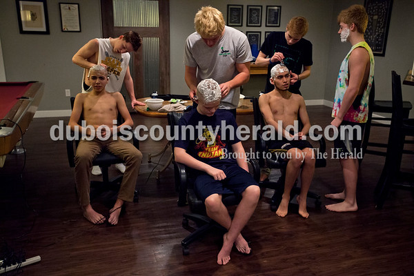 """Alisha Jucevic/The Herald   Jasper High School junior Max Henke, far right, watched freshman Abraham De La Cruz, left, Andrew Head and senior Luis Lopez as they sat still for junior Nolan Henke, left, Matt Head and Jason Fleck on Wednesday evening in Jasper.  """"Do you guys feel faster?"""" Nolan and Max's dad, Mark joked with the boys. This was the second year the team came over to the Henke household to cut their hair. Mark said it's always fun to see the younger guys reaction after the first time they get a completely shaved head."""