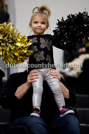Kynzlee Voegerl of Jasper, 2, stood on the knees of her grandmother Angie Schue of Jasper to cheer during Tuesday's basketball game in Jasper. Jasper defeated Princeton 55-52. Sarah Ann Jump/The Herald