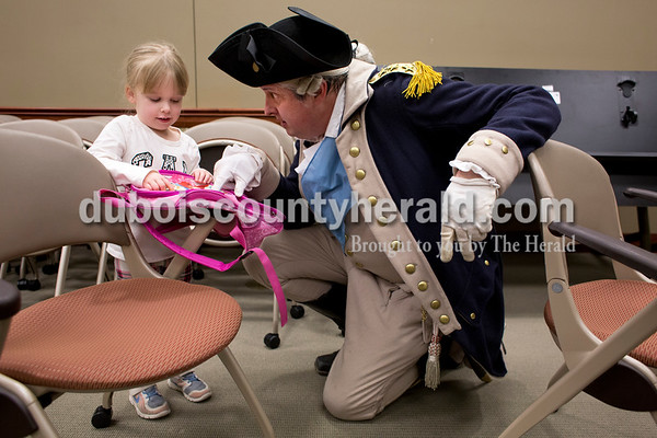 Sarah Ann Jump/The Herald Ella Robinson of Jasper, 4, showed George Washington presenter David Wolfe of Owensboro, Ky. her backpack and together they named all of the Disney princesses on it after Wolfe's presentation about the life of George Washington at the Ferdinand Library on Wednesday.