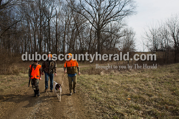 Sarah Ann Jump/The Herald From left, Reece Fromme of Ireland, 13, his father Todd Fromme and Derek Roth of Huntingburg walked back from the hunting fields with Roth's German shorthaired pointer Ollie during the Patoka Hills Wes Settle Youth Quail Hunt at Cane Creek Hunting Preserve in Otwell on Saturday.