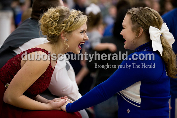 Northeast Dubois sophomore Hannah Schepers, a member of the homecoming court, left, laughed with her cheerleading teammate junior Kristin Blessinger before Friday's homecoming basketball game in Dubois. Northeast Dubois defeated Loogootee 58-56. Sarah Ann Jump/The Herald