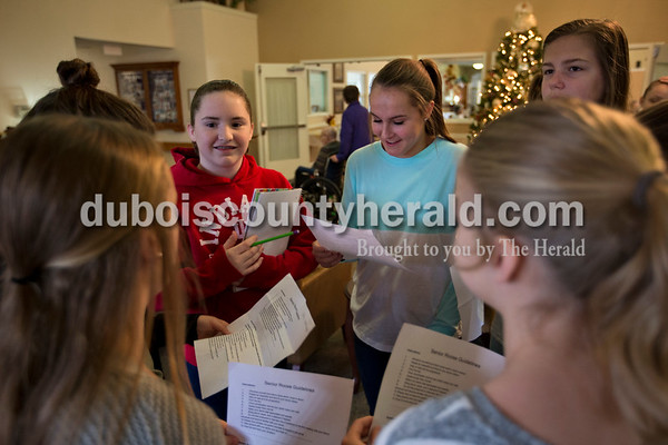 Jasper Middle School seventh-graders Cara Adams, left, and Mya Stiles, right, checked in with project organizer Marianna Green and the other ROOS club members in the lobby at Brookside Village Senior Living Community before meeting their seniors for the first time on Nov. 19 in Jasper. Marianna typed up a list of question ideas for each group of students to bring with them when they met with their senior.