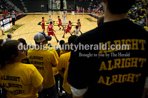 """Jasper's Eric Nordhoff made a basket during Tuesday's basketball game in Jasper. The Jasper student section wore gold and black shirts in memory of Frankie Ebenkamp. The back of the shirt featured Ebenkamp's famous chant """"Alright, alright, alright."""" Jasper defeated Princeton 55-52. Sarah Ann Jump/The Herald"""