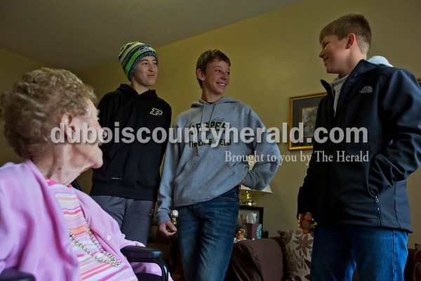 """Jasper Middle School eighth-graders Will Messmer, left, Bennett Schmitt, and William Schmitt chatted with resident Sally Rees during the ROOS club's first visit to Brookside Village Senior Living Community on Nov. 19 in Jasper.  """"It will be amazing to see what things are like when you guys get to my age,"""" Rees said to the boys."""