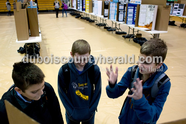 Tegan Johnston/The Herald Jasper Middle School seventh-grader Jordan Krempp, left, showed his project to his friends seventh-graders Carter Hopf, center, and Gabe Schmitt before the annual science fair at Jasper Middle School Wednesday morning in Jasper. Students presented their projects to judges throughout the day and an overall 6th, 7th, 8th and invention winner will be announced tomorrow evening at 6:30.
