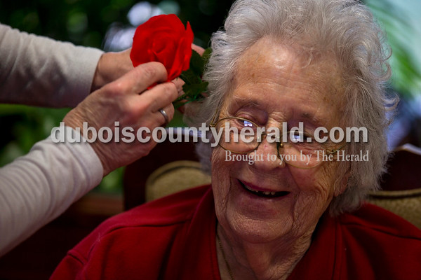 Alisha Jucevic/The Herald   In celebration of Valentine's Day on Tuesday afternoon Jasper's Northwood Retirement Community gathered their residents for a sweetheart social and old time love songs. Activities assistant Jan Egg placed a rose in resident Lucille Garland's hair during the event.
