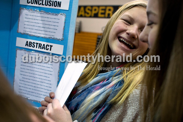 """Tegan Johnston/The Herald Jasper Middle School Mackenzie Belk laughed while talking about her project """"Freeze and Ease"""" to her friends Kendalyn Hurm, right, and Marianna Green, all in seventh-grade, before the annual science fair at Jasper Middle School Wednesday morning in Jasper. Students presented their projects to judges throughout the day and an overall 6th, 7th, 8th and invention winner will be announced tomorrow evening at 6:30."""