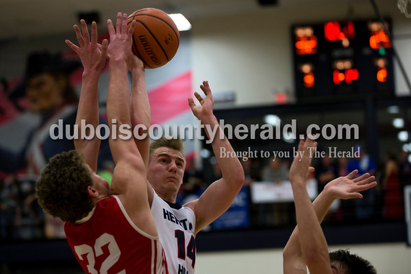 Heritage Hills' Grant Doyle went up for a shot against Tell City's Braeden Beard during Friday night's game against Tell City in Lincoln City. Heritage Hills won 41-40.   Alisha Jucevic/The Herald