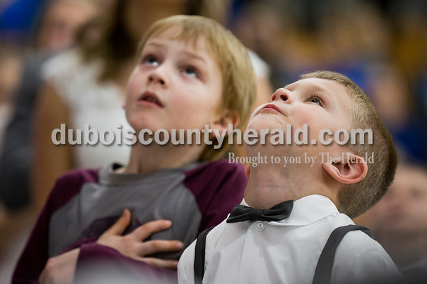 Travis Weyer, 6, left, and Cort Everman of Haysville, 6, looked up at the American flag hanging above them during the national anthem before Friday's homecoming basketball game in Dubois. Northeast Dubois defeated Loogootee 58-56. Sarah Ann Jump/The Herald