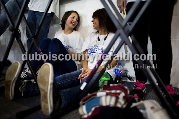 Northeast Dubois pep band sophomores Madison McIntosh and Lisette Moya talked as they sat under an xylophone during Friday's homecoming basketball game in Dubois. Northeast Dubois defeated Loogootee 58-56. Sarah Ann Jump/The Herald