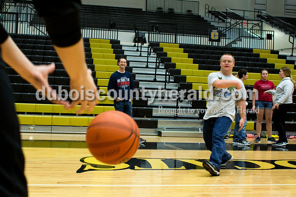 Tegan Johnston/The Herald Adam Schwartz of Jasper bounced a basketball to a Jasper basketball player during a local Special Olympics activity hosted by Jasper High School's Business Professionals of America and the boys basketball team on Saturday afternoon at Jasper High School in Jasper. The Special Olympic athletes shot hoops and participated in various activities with the Jasper players.
