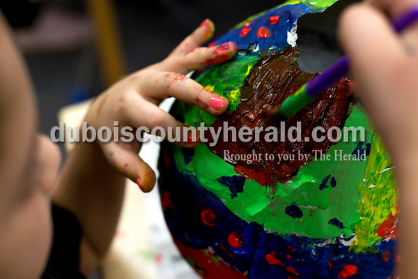 Tegan Johnston/The Herald Huntingburg second-grader Rosi Serrano mixed colors on her papier-mâché pinata during a RIDGE art class at Huntingburg Elementary School Tuesday afternoon in Huntingburg. The after-school program offered a variety of clubs that alternate every 3 and a half weeks. Currently, students can choose between cooking, video taping, origami, art and reading clubs.