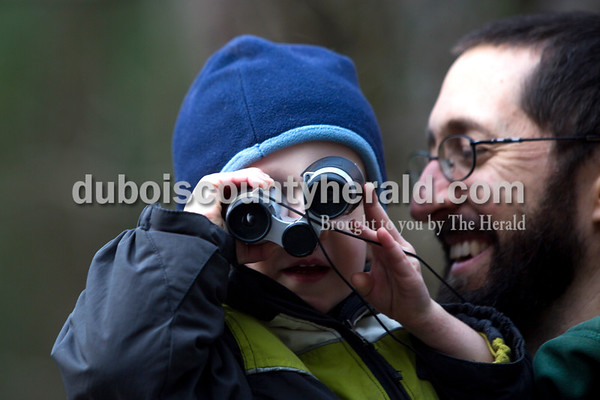 Tegan Johnston/The Herald William Schemenauer of Ferdinand, 2, looked through his binoculars while his father Kevin carried him during the Cabin Fever Hike at Ferdinand State Forest in Ferdinand. Adventures Recreation & Gear helped sponsor the 2.5 and 5.5-mile hikes by offering a prize giveaway. Participants of the free event were asked to donate a non-perishable food item for the Dubois County Food Bank.