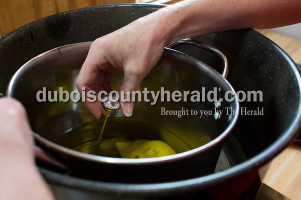 Sarah Ann Jump/The Herald Patty Ruhe measured the temperature of a mixture of oils in a double boiler for a batch of chocolate peppermint soap in her home workshop near Maltersville on Monday.