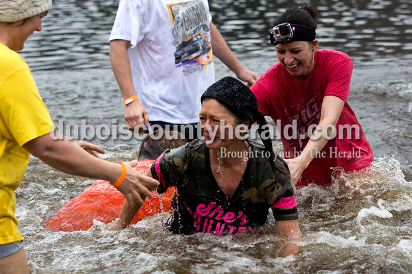 Tegan Johnston/The Herald Theresa Schwartz was helped out of the water by her friend Diane Rickelman, left, and her daughter Lauren, all of Ferdinand, during the annual Dubois County Polar Plunge on Sunday afternoon at Ferdinand State Forest in Ferdinand. Schwartz said she was scared of water, but did the plunge in honor of her sister who is battling colon cancer. Proceeds from the event benefitted the Lange-Fuhs Cancer Center, Dubois County Leukemia Association and area food banks.