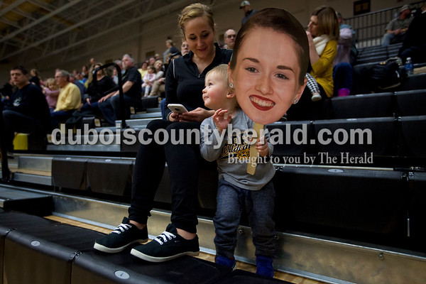 Jasper dance coach Jordan Beach sat with her son Porter, 2, as he held a sign of one of his favorite dancers, Paige Green, during Tuesday night's game against North Daviess in Jasper. The Wildcats won 60-48.   Alisha Jucevic/The Herald