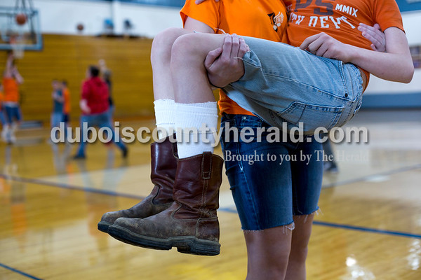 Tegan Johnston/The Herald Northeast Dubois freshman Fantasy Wright picked up freshman Colby Stafford in the gym after lunch Thursday. The school dressed to remember their classmate Chad Knies who passed in a car accident Sunday. The students wore orange shirts that match the color of his favorite tractor, cut-off jean shorts and high, white socks with boots or black tennis shoes which the students said he would always wear.