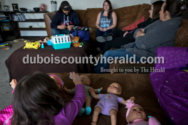 Sanders and her midwife assistant, Hanna Caywood, of Odon chatted with Cortney and her husband, Jose, as their daughter Kyndle, 3, played with dolls beside them Jan. 6.