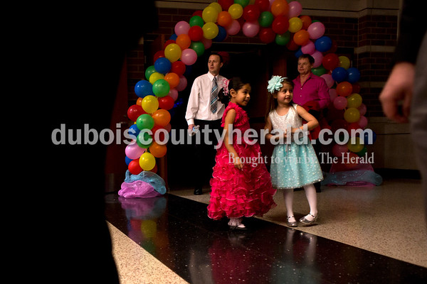 Tegan Johnston/The Herald Arianna Jara, 5, left, and Leah Mattingly, 6, both of Jasper, watched as people arrived to the second annual Daddy and Daughter Dance on Saturday evening at Jasper Middle School in Jasper.  Dance Central Academy Parent Club sponsored the event that drew over 300 people.