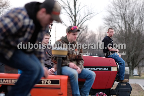 Southridge High School sophomore Blake Lindauer, right,  sat on the front of his tractor Tuesday morning in the school's parking lot during Drive Your Tractor To School Day. Dave Weatherwax/The Herald