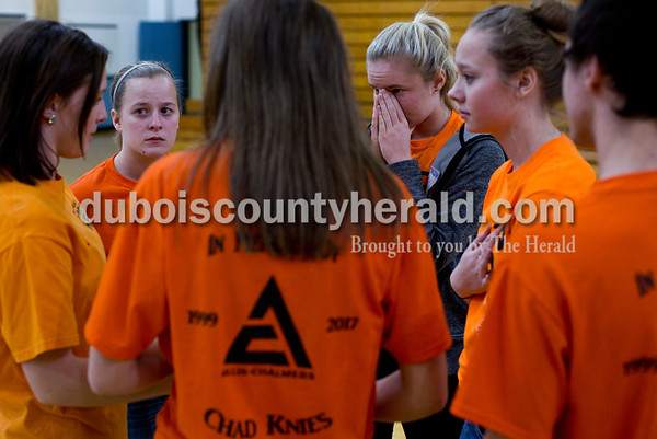 Tegan Johnston/The Herald Northeast Dubois Senior Jessica Kahle, second from left, and freshman Amberly Jacob listened to freshman MaKena Everman, left, talk to her classmates after lunch Thursday. The school dressed to remember their classmate Chad Knies who passed in a car accident Sunday. The students wore orange shirts that match the color of his favorite tractor, cut-off jean shorts and high, white socks with boots or black tennis shoes which the students said he would always wear.