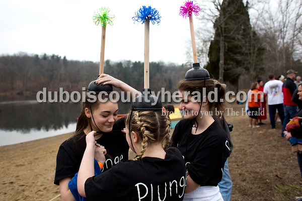 Tegan Johnston/The Herald Gracie Graves of Ferdinand, 13, secured Kristen Detty's plunger hat, of Birdseye, 13, as Kendall Barth of Ferdinand, 13, watched before their first time participating in the annual Dubois County Polar Plunge on Sunday afternoon at Ferdinand State Forest in Ferdinand. Proceeds from the event benefitted the Lange-Fuhs Cancer Center, Dubois County Leukemia Association and area food banks.