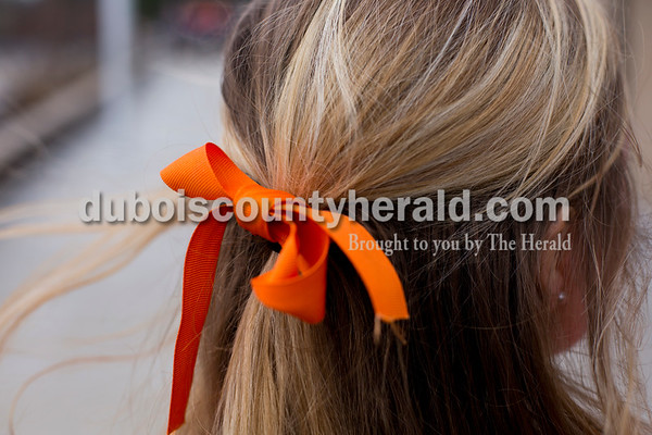 Tegan Johnston/The Herald Northeast Dubois senior Melanie Roberts tied an orange ribbon in her hair Thursday. The school dressed to remember their classmate Chad Knies who passed in a car accident Sunday. The students wore orange shirts that match the color of his favorite tractor, cut-off jean shorts and high, white socks with boots or black tennis shoes which the students said he would always wear.