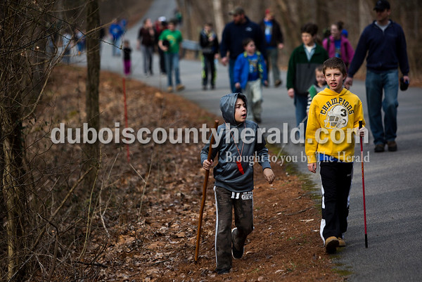 Tegan Johnston/The Herald Trent Tyree of Ferdinand, 9, left, talked to Conner Hochugesang of Ferdinand, 8, while they hiked during the Cabin Fever Hike at Ferdinand State Forest in Ferdinand. Adventures Recreation & Gear helped sponsor the 2.5 and 5.5-mile hikes by offering a prize giveaway. Participants of the free event were asked to donate a non-perishable food item for the Dubois County Food Bank.