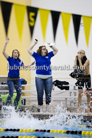Northeast Dubois assistant coach Kendra Friedman, left, head coach Jennifer Wright and Jasper's Abraham De La Cruz cheered on their teams during the 200-yard freestyle relay at Saturday's boys swimming sectional in Jasper. The Northeast Dubois relay team placed sixth with a time of 1:43.97, which the coaches said was a personal best. Sarah Ann Jump/The Herald