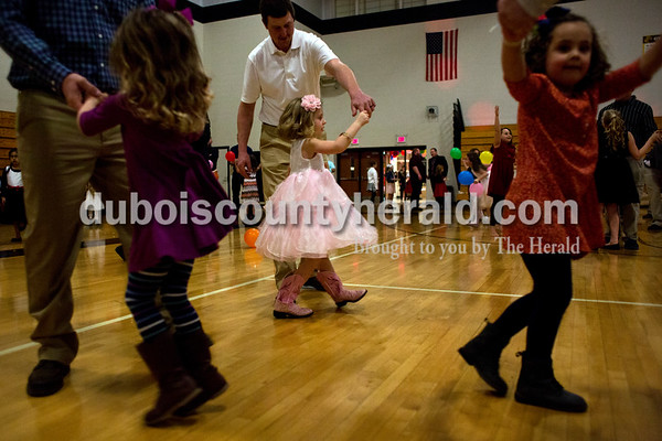 Tegan Johnston/The Herald Kyle Hochgesang of Jasper, center, twirled his daughter Reagan, 5, during the second annual Daddy and Daughter Dance on Saturday evening at Jasper Middle School in Jasper.  Dance Central Academy Parent Club sponsored the event that drew over 300 people.