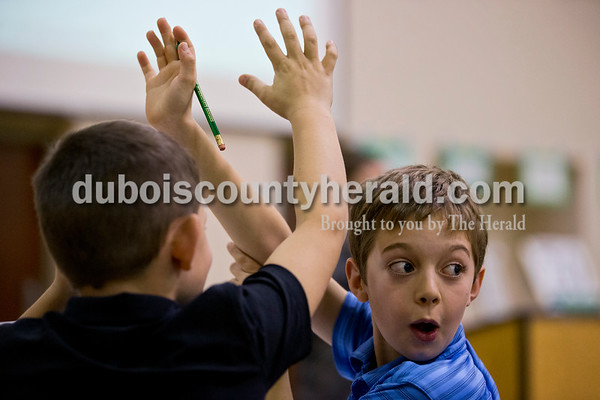 Ireland Elementary fourth-grader Caleb Schnarr, left, and fifth-grader Carson Bauer celebrated a correct answer during the 21st Annual Indiana Academic M.A.T.H. Bowl at Cedar Crest Intermediate School on Thursday. Ireland Elementary placed first in their division.     Alisha Jucevic/The Herald