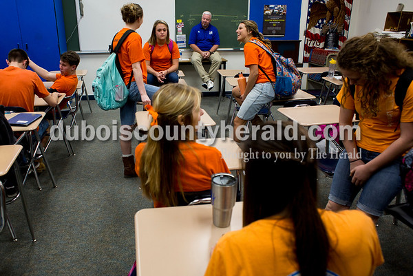 Tegan Johnston/The Herald Northeast Dubois High School teacher Brian Kirchoff sat at the front of the room and talked to his class of seniors after their Psychology lesson Thursday. The school dressed to remember their classmate Chad Knies who passed in a car accident Sunday. The students wore orange shirts that match the color of his favorite tractor, cut-off jean shorts and high, white socks with boots or black tennis shoes which the students said he would always wear.