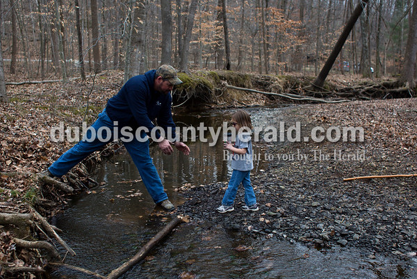 Tegan Johnston/The Herald Dana Tyree of Ferdinand lifted Analyse DeWitte of Kyana, 4, across a creek after the Cabin Fever Hike at Ferdinand State Forest in Ferdinand. Adventures Recreation & Gear helped sponsor the 2.5 and 5.5-mile hikes by offering a prize giveaway. Participants of the free event were asked to donate a non-perishable food item for the Dubois County Food Bank.