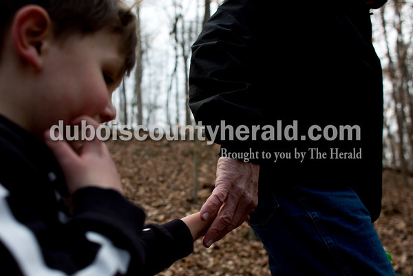 Tegan Johnston/The Herald Lee Striegel of Jasper held the hand of his great-grandson Greyson Denton of Huntingburg, 3, as they hiked along the trail during the Cabin Fever Hike at Ferdinand State Forest in Ferdinand. Adventures Recreation & Gear helped sponsor the 2.5 and 5.5-mile hikes by offering a prize giveaway. Participants of the free event were asked to donate a non-perishable food item for the Dubois County Food Bank.