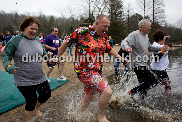 Tegan Johnston/The Herald Andrew Verkamp of Kyana, center, and his wife, Cheryl, charged into a frigid lake during their first time participating in the annual Dubois County Polar Plunge on Sunday afternoon at Ferdinand State Forest in Ferdinand. Proceeds from the event benefitted the Lange-Fuhs Cancer Center, Dubois County Leukemia Association and area food banks.