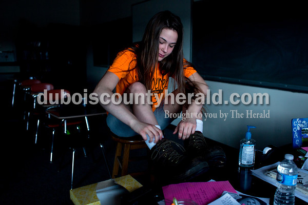 Tegan Johnston/The Herald Northeast Dubois sophomore Sierra Ward tied her boots before the bell during Ms. Jessica Pfau's English 10 class Thursday. The school dressed to remember their classmate Chad Knies who passed in a car accident Sunday. The students wore orange shirts that match the color of his favorite tractor, cut-off jean shorts and high, white socks with boots or black tennis shoes which the students said he would always wear.