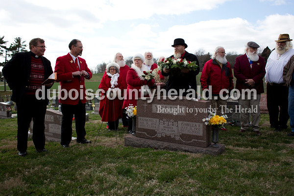 """Tegan Johnston/The Herald Timothy Etter of Fishers, center, presented a wreath to be laid at Raymond Joseph """"Jim"""" Yellig headstone after the presentation of the Sagamore of the Wabash award to Pat Koch on behalf of her late father, Yellig, Saturday at Mary Help of Christians Catholic Church in Mariah Hill. The award is Indiana's highest civilian award given to a Hoosier by the governor for a great service to the state or to the governor. Yellig was honored for his service as Santa Claus by responding to children's letters, spreading the Christmas joy and preserving the faith of children."""