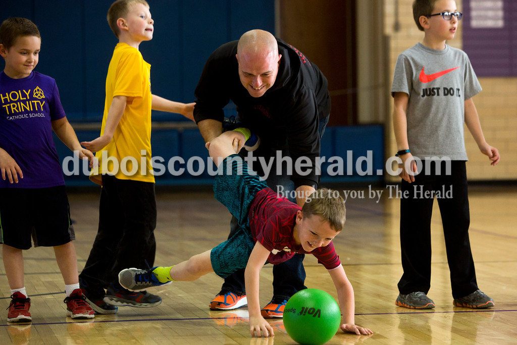 Tegan Johnston/The Herald<br /> Adam Bower of Jasper held onto the legs of Holy Trinity second-grader Ryan Kelly as he reached for a dodge ball during Holy Trinity Family Dodge Ball Night at Holy Family's East Campus Gymnasium in Jasper on Friday night. The school hopes to start having monthly dodge ball games where students can play together and get to know their classmates. From 6-7:30 p.m. second through fourth grade students can play with their parents, and from 7:30-9 p.m. fifth through eighth grade students can compete.