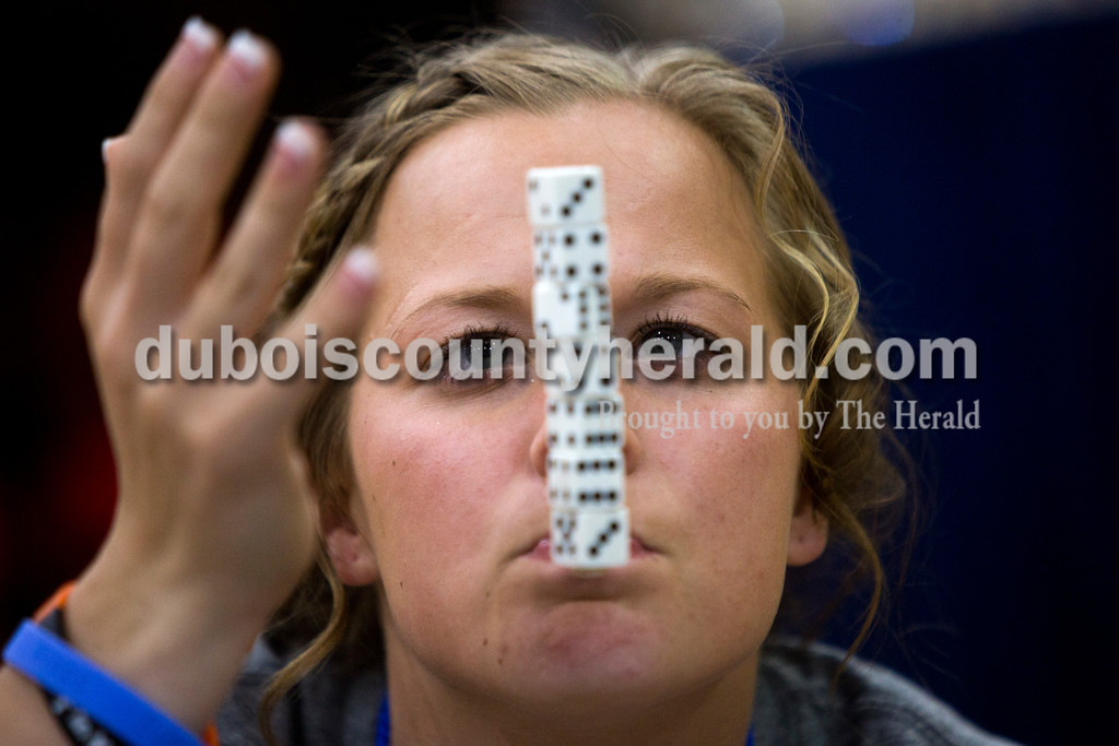 """Tegan Johnston/The Herald<br /> Northeast Dubois senior Jessica Kahle stacked seven dice on a popsicle stick while playing """"Minute to Win It"""" during the school's post-prom party on Saturday evening. Juniors and seniors gathered with their guests in the high school gym to enjoy the Hollywood-themed event's variety of games and refreshments."""