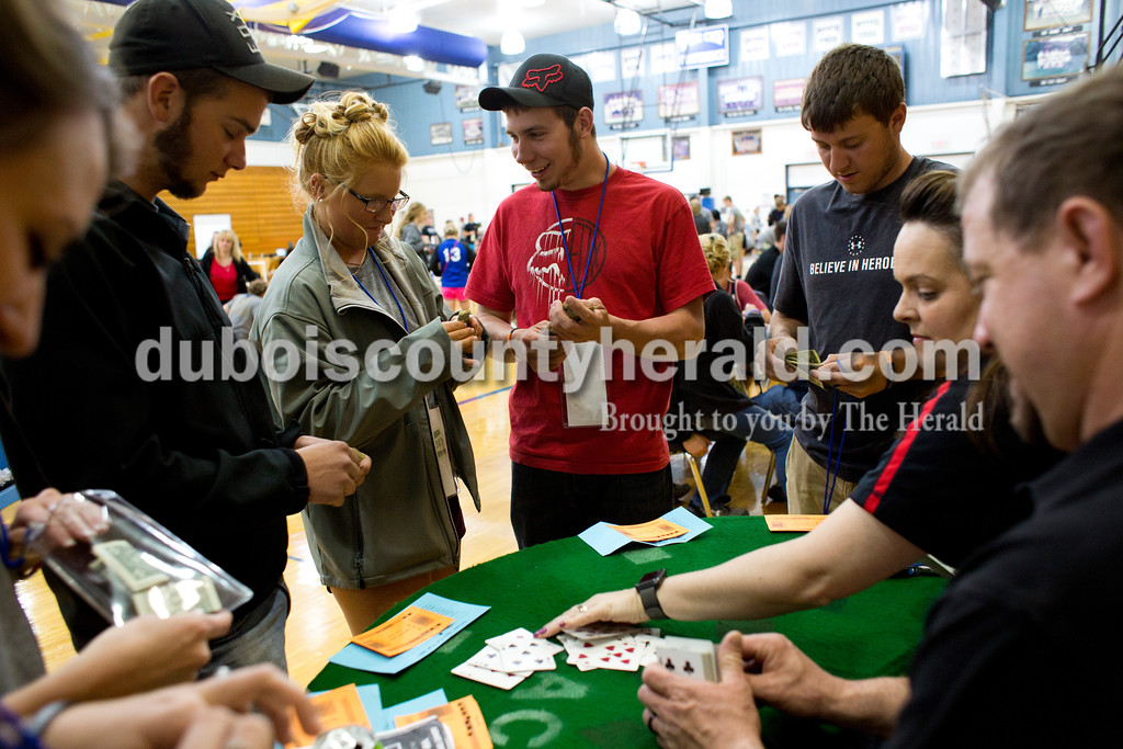 Tegan Johnston/The Herald<br /> Northeast Dubois senior Curtis Gress, center, talked to senior Harlee Zehr after winning a dollar while playing a card game during the school's post-prom party on Saturday evening. Juniors and seniors gathered with their guests in the high school gym to enjoy the Hollywood-themed event's variety of games and refreshments.