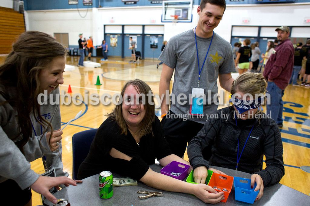 Tegan Johnston/The Herald<br /> Northeast Dubois senior Savannah Stafford sorted nuts and bolts while playing a game as her date, Forest Park senior Reid Brown, held her blindfold during the school's post-prom party on Saturday evening. Juniors and seniors gathered with their guests in the high school gym to enjoy the Hollywood-themed event's variety of games and refreshments.