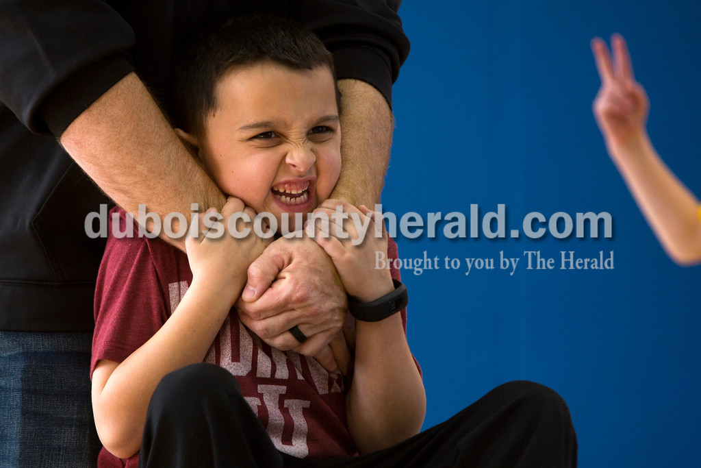Tegan Johnston/The Herald<br /> Holy Trinity second-grader Mason Bower held on to his father, Adam, as he hung from his arms during Holy Trinity Family Dodge Ball Night at Holy Family's East Campus Gymnasium in Jasper on Friday night. The school hopes to start having monthly dodge ball games where students can play together and get to know their classmates. From 6-7:30 p.m. second through fourth grade students can play with their parents, and from 7:30-9 p.m. fifth through eighth grade students can compete.