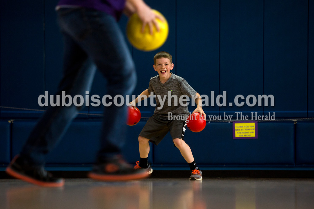 Tegan Johnston/The Herald<br /> Holy Trinity fourth-grader Samuel Kelly armed himself with two dodge balls while playing during Holy Trinity Family Dodge Ball Night at Holy Family's East Campus Gymnasium in Jasper on Friday night. The school hopes to start having monthly dodge ball games where students can play together and get to know their classmates. From 6-7:30 p.m. second through fourth grade students can play with their parents, and from 7:30-9 p.m. fifth through eighth grade students can compete.